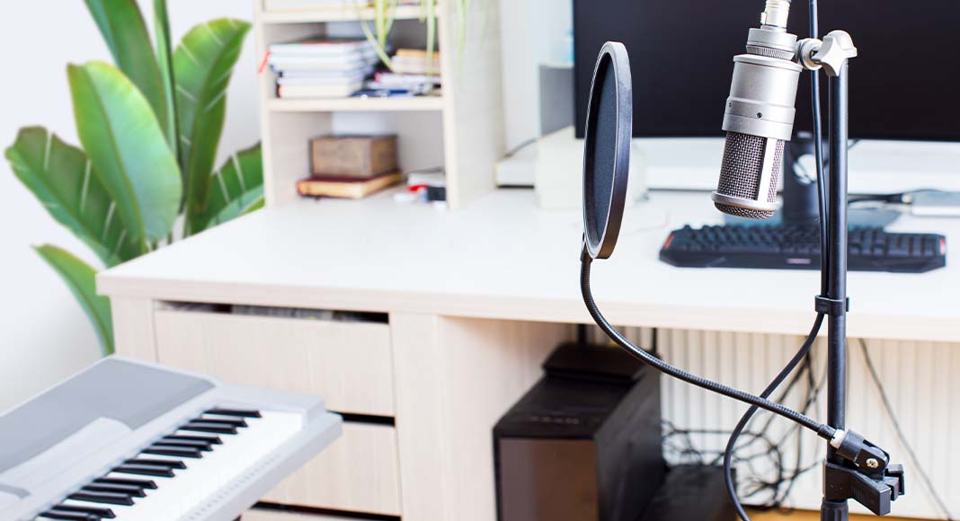 Voice over microphone positioned next to a keyboard and a computer screen