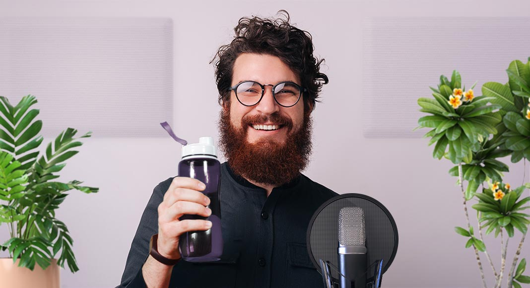 Smiling bearded voice actor holding a water bottle