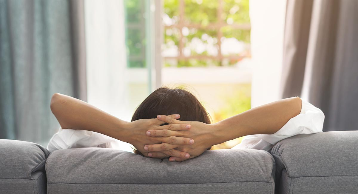 Viewed from behind, a woman relaxes on a couch and supports her head in her hands