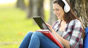 Girl sits by a tree with headphones looking at a tablet