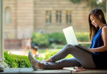 A young woman, presumably listening to her elearning course, sits outside in a school courtyard with her laptop on her lap.