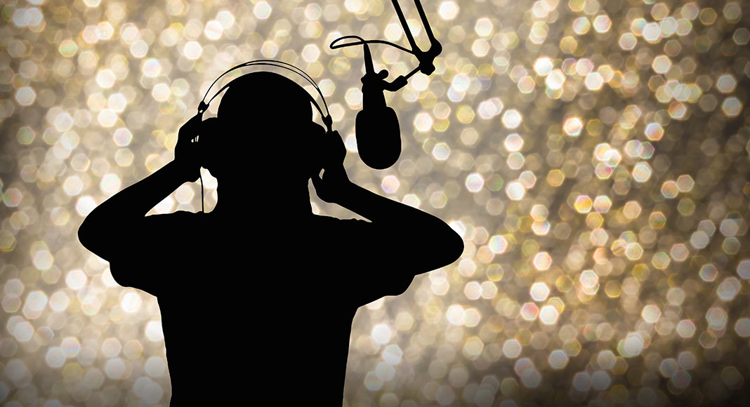 Image depicting a silhouette of a person with headphones on and the outline of a microphone.