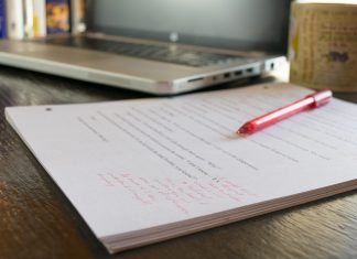 A manuscript and laptop on a table. The manuscript shows red pen markings to show how a narrator makes notes in the margins of a book to help themselves prepare for the narration recording.