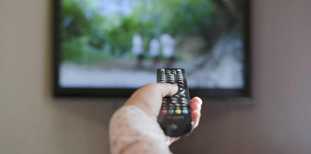a woman's hand holding a TV remote towards the TV with a national geographic style show playing on the TV, signifying the different accents and languages found in american media and marketing