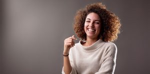 A young woman in a cream colored sweater against a dark backdrop has her right hand slightly lifted and is clearly laughing, joyfully.