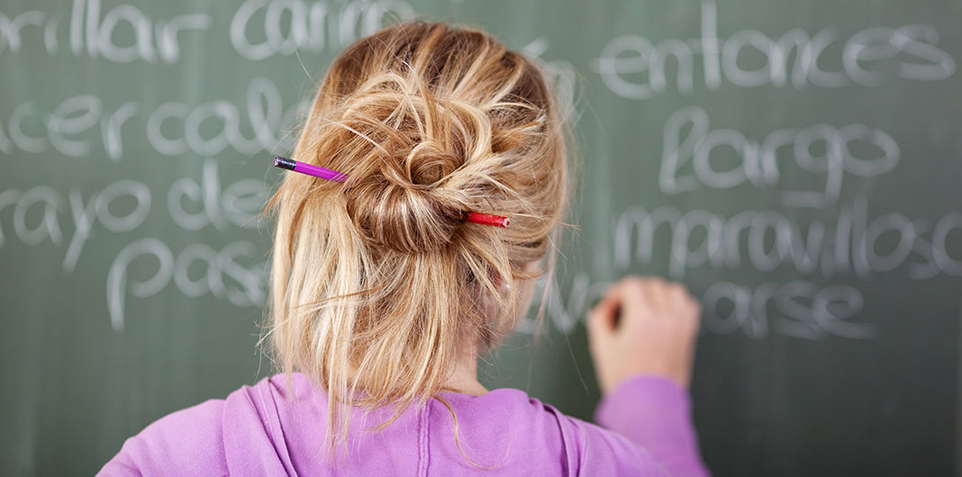A blonde haired woman writing spanish words on a chalk board, signifying the learning of Spanish.