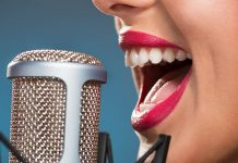 a close up photo of a woman singing into a condenser microphone
