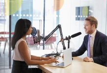 A woman interviewing a man for a podcast in a contemporary and branded office setting.