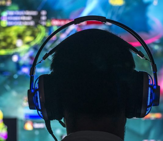 Silhouette of a video game plater wearing headphones with an out-of-focus video game screed in the background.