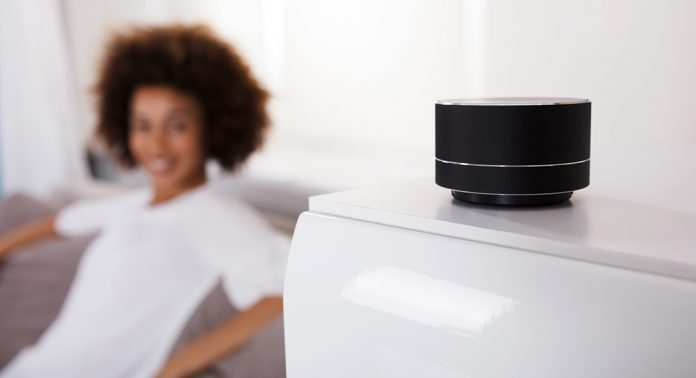 an Amazon Smart Speaker sitting on an end table next to a woman who looks pleased to own the smart speaker.