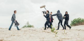 A young male vagabond is walking in the barren desert-like wilderness with a film crew following close behind.