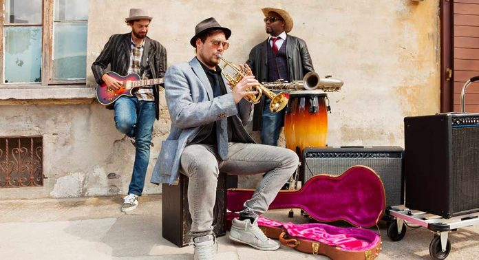 A blues band is jamming out on the side of the street looking real relaxed.