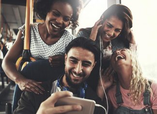 A group of four young adults gather together to listen to and watch what is on their friend's cellphone. They're all laughing and looking like they're having a good time.