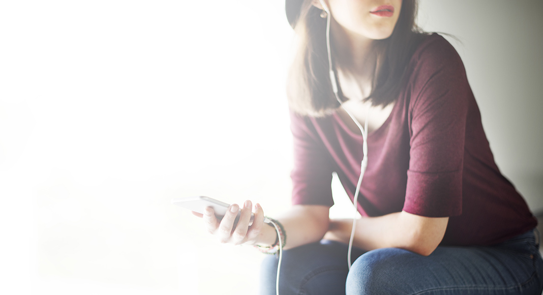 A woman sits with her phone in one hand and headphones in her ears. She appears to be listening intently.