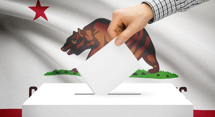 Image of man's hand putting ballot in box with California flag in background.