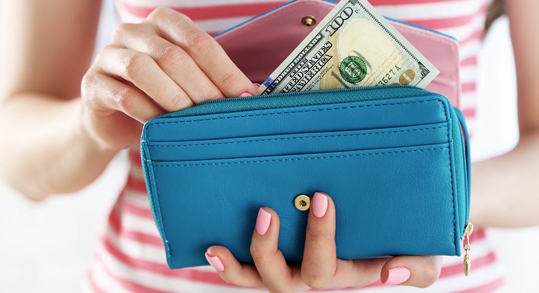 Woman clutching a blue wallet filled with money