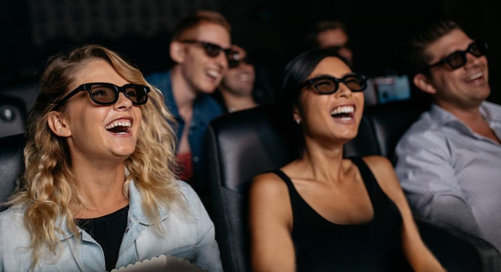 Group of people laughing in a dark movie theatre