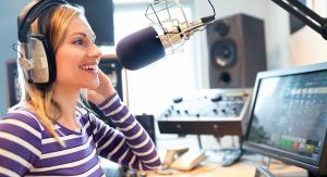 Happy female radio host broadcasting in studio