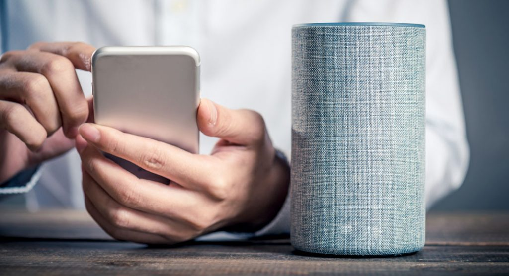 Man using a phone and smart speaker