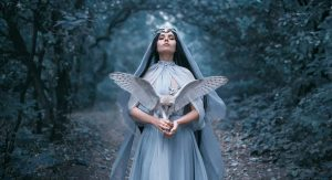 A mystical woman holds an owl.
