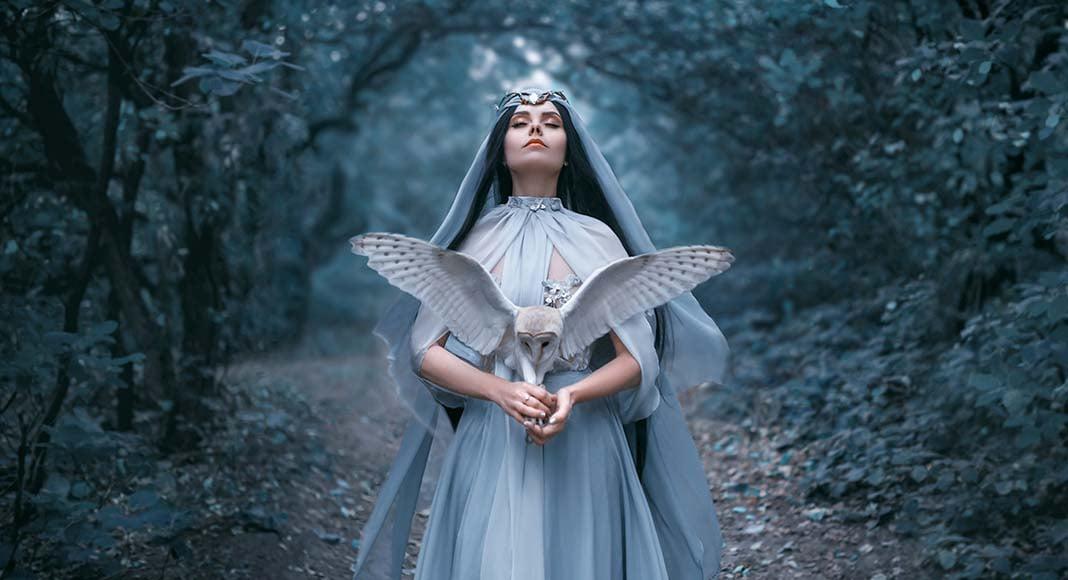 A mystical woman holds an owl.