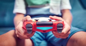 Red video game controller being held by a young man