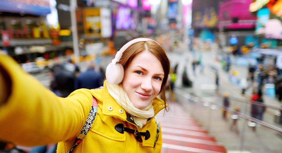 A young woman with headphones in a crowded Times Square