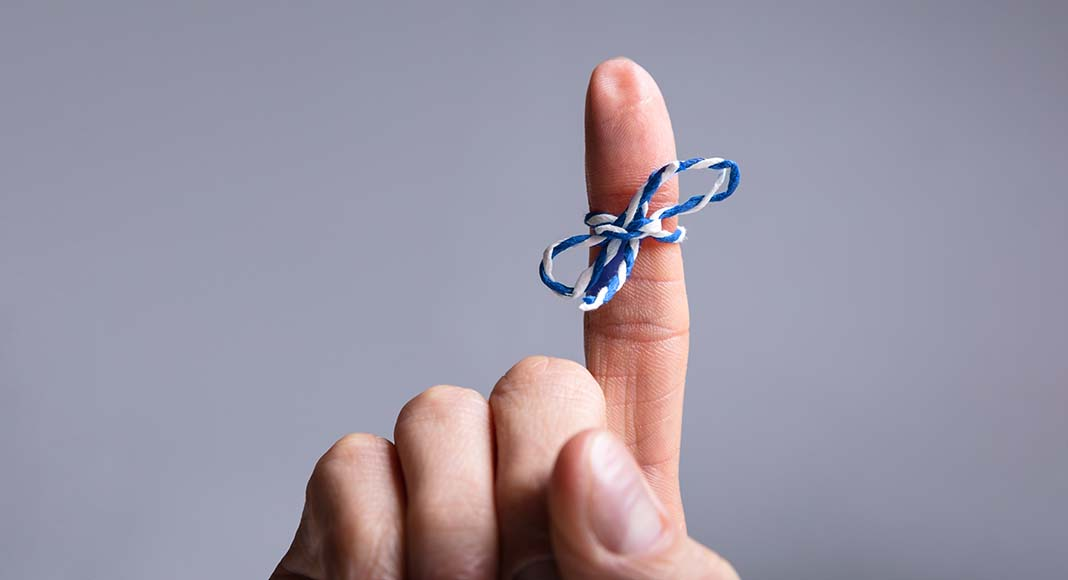 Index finger with string bow tied around it