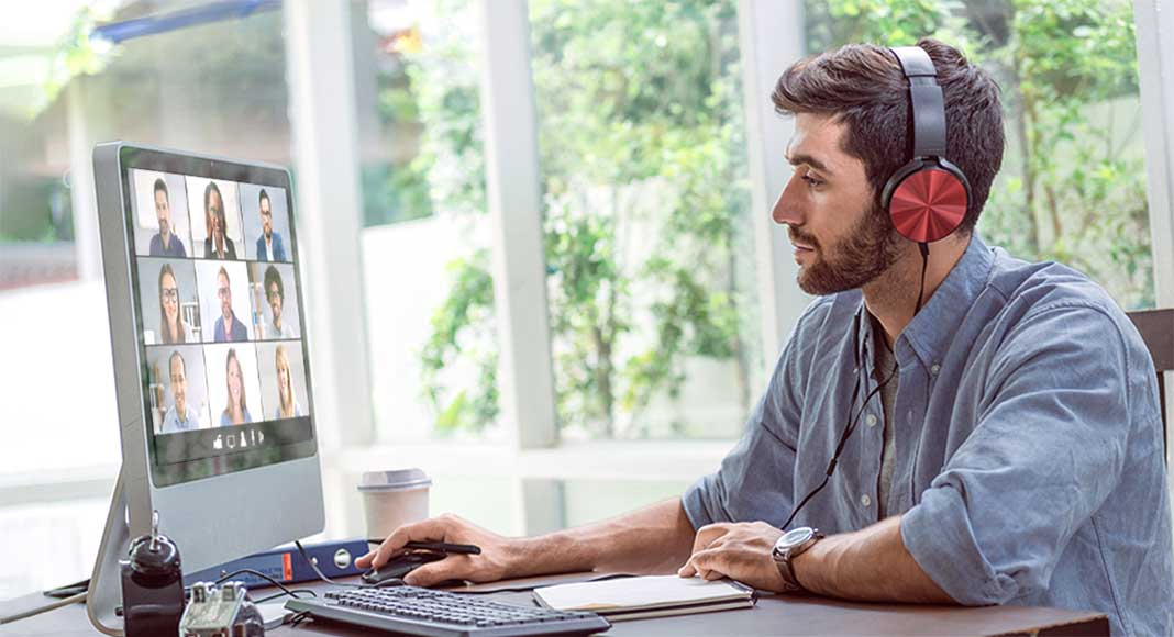 Young man wearing headphones at computer screen with video conference call