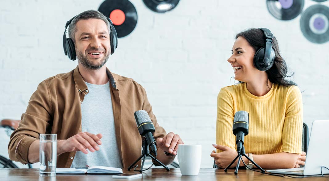 Two jovial podcasts hosts sit with microphones