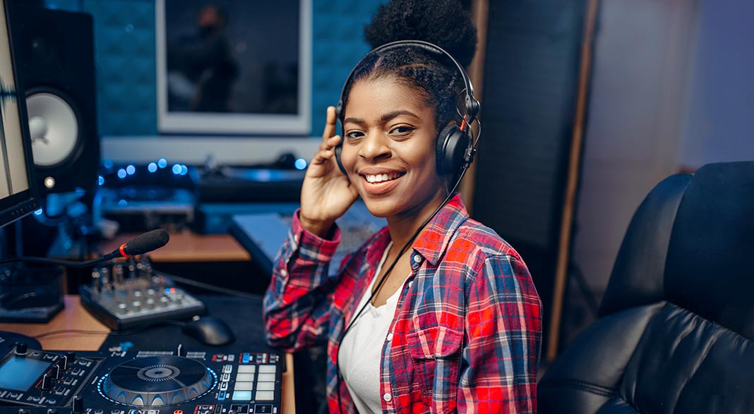 Young smiling woman sits in recording studio wearing headphones