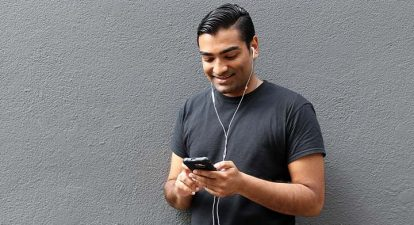 A man with dark hair and ear buds in his ears, holds his cellphone in both hands and smiles, enjoying what he is listening to.