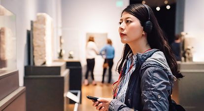 Dark-haired woman listening to audio recording at a museum