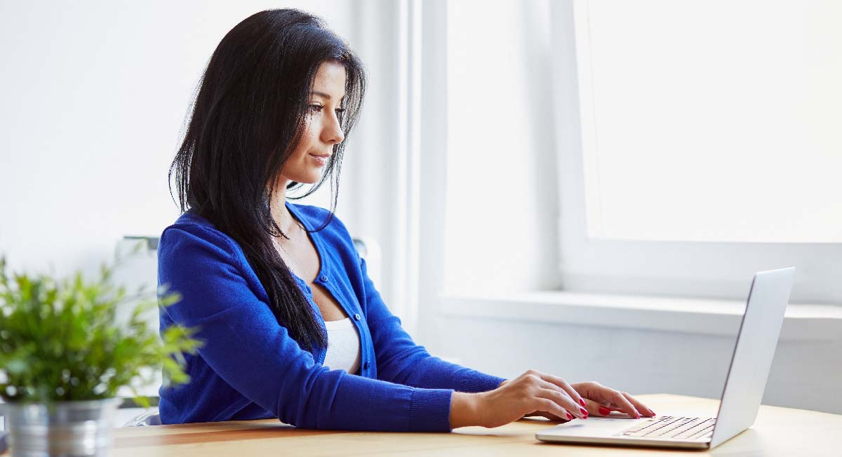 Woman with dark hair sitting and using laptop