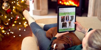 Woman sits by Christmas tree and fireplace with dog on her lap while online shopping using tablet