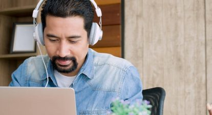 man sitting at a laptop with silver headphones on. Image for a blog post on the top 5 sound effect websites