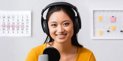 Female voice actor wearing headphones while recording her voice at microphone equipped with pop filter