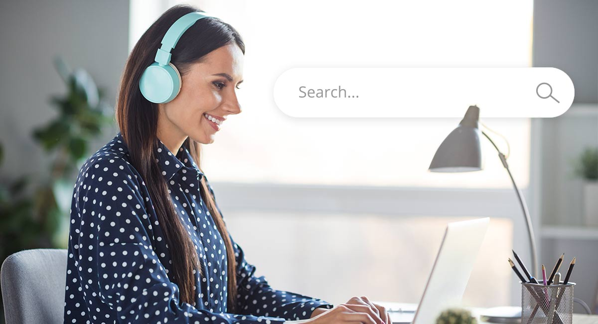 Person listening to audio on headphones while searching the internet
