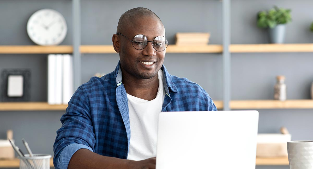 Smiling young man wearing round glasses and an open blue plaid dress shirt over a white tee works at his laptop in a home office