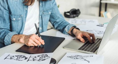 Animator working from home, sitting at a desk with a laptop, transferring drawn sketches from paper to a tablet using a stylus pen