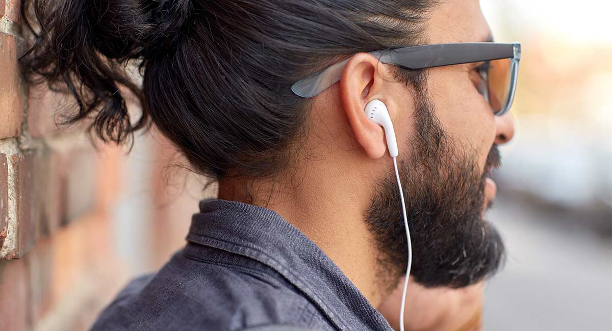 man with ear buds listening to jingles of the 2000s