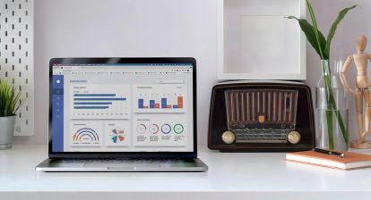 A laptop with analytics on the screen next to a radio