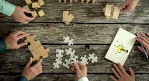 The hands of five people are placed on a table, each one working away at a puzzle or sketching out a solution to a problem.