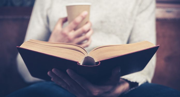 A person sits with a coffee in one hand and an open book in their lap