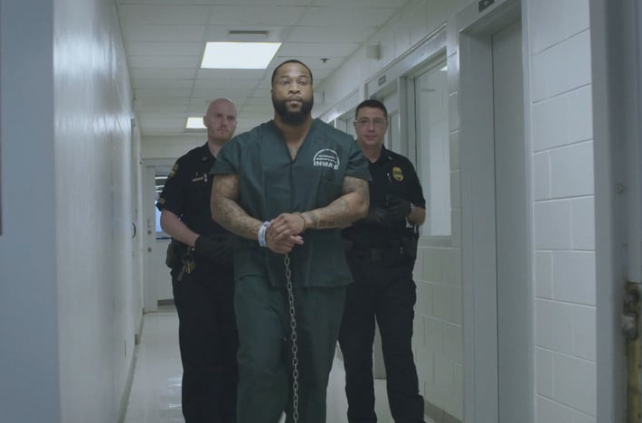 Screen shot of a prisoner being walked down a prison hallway by two guards. Screen shot from documentary 'By the Riches of His Grace'