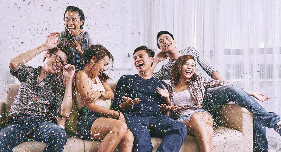 A group of friends sit on a couch, laughing as confetti rains down
