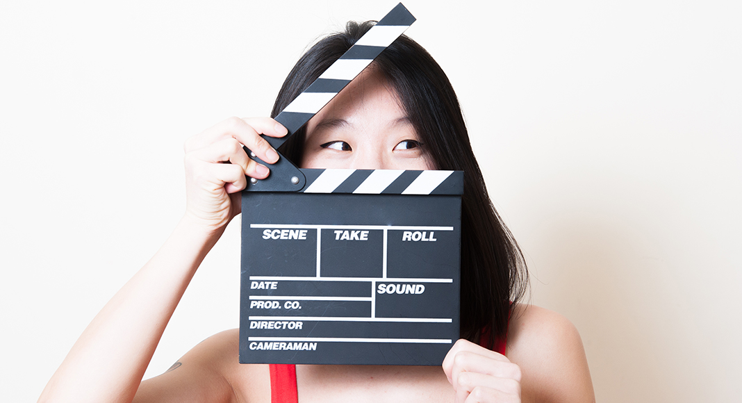 A woman stands with a clapperboard in front of her face.