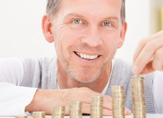 A man with blue eyes and gray hair smiles and looks at the camera as he stacks coins in several rows.