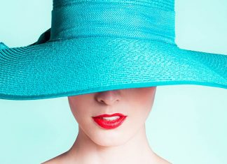 the lower portion of a woman's face is visible from underneath a high fashion hat
