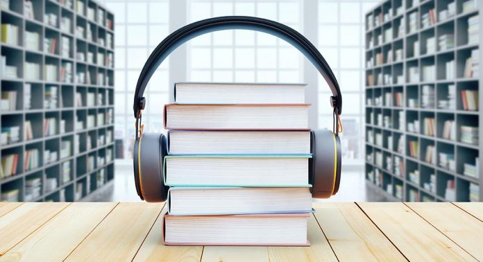A stack of books sits on a table, with a library visible in the background. A pair of headphones is wrapped around the stack of books.